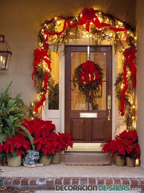 puerta navideña decorada con flor de pascua
