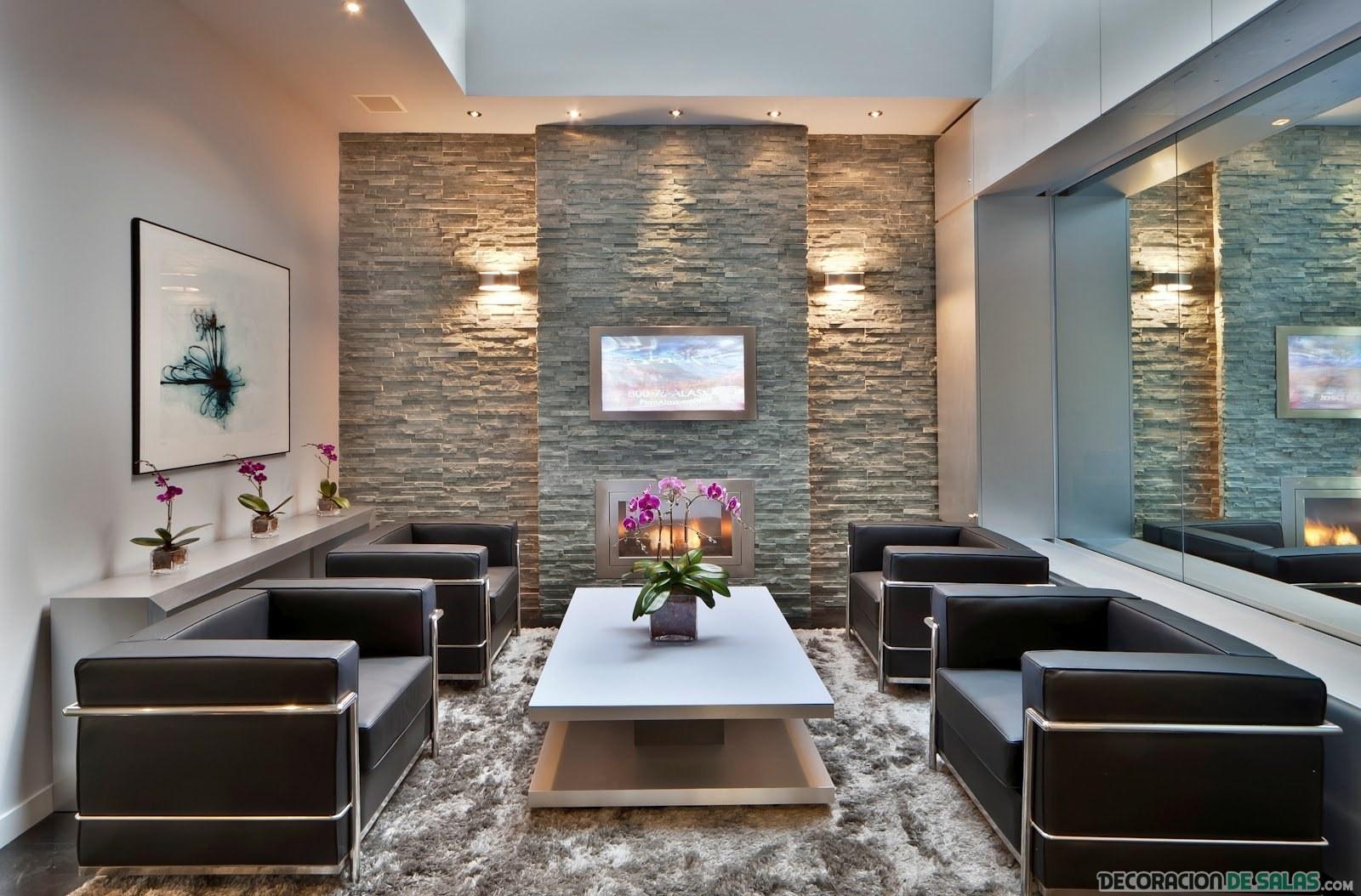 salón con paredes de piedra y sofás en negro